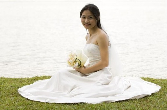 A beautiful young woman sits on a grassy bank in her wedding dress